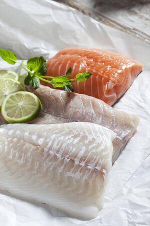 haddock: Fish fillets, haddock, coalfish and salmon, limes and herbs on greaseproof paper