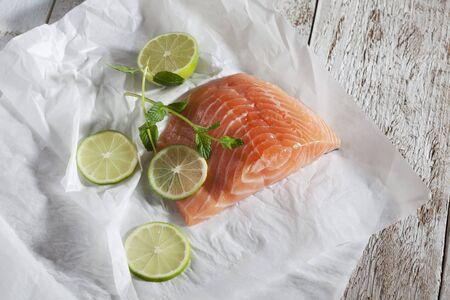 filete de pescado: Filete de pescado, salm�n, limas y hierbas sobre papel de horno, madera Foto de archivo