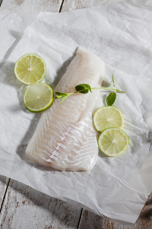 Fish fillet, haddock, limes and herbs on greaseproof paper