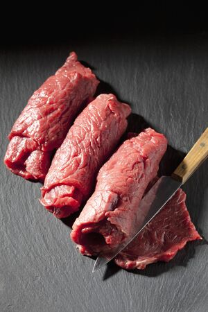 schist: Row beef roulades and knife on slate Stock Photo