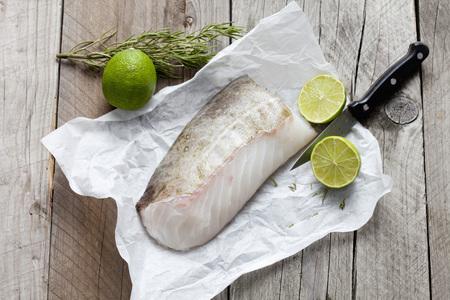 codfish: Row fish fillet, codfish on greaseproof paper Stock Photo