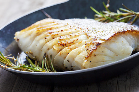 food fish: Fried fish fillet, Atlantic cod with rosemary in pan Stock Photo