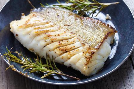 Gebakken visfilet, Atlantische kabeljauw met rozemarijn in de pan Stockfoto