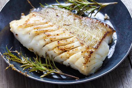 Fried fish fillet, Atlantic cod with rosemary in pan Standard-Bild