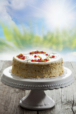 cakestand: Wine cream cake on cake stand, on wood, sunshine Stock Photo