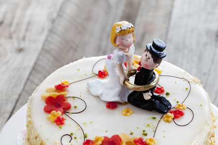 pastel de bodas: Vino pastel de crema, torta de la boda con las estatuillas, la novia y el novio Foto de archivo