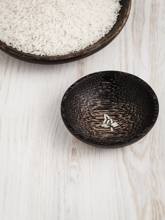 unfairness: Unboiled rice distributed  in wooden bowls