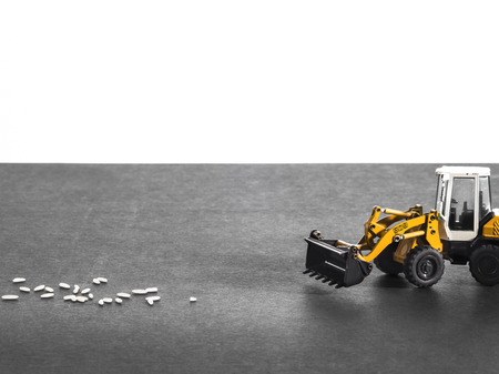unfairness: Toy digger on pile of rice, staple, distribution, trade