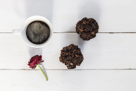 cofffee: Cup of cofffee, chocoloate muffins and buttercup blossom on wood