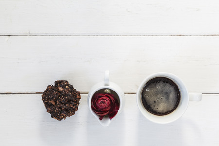 cofffee: Cup of cofffee, chocoloate muffin and buttercup blossom on wood Stock Photo