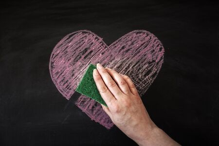 lovelorn: Hand removing chalk heart from black board