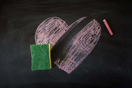 lovelorn: Sponge removing chalk heart from black board Stock Photo