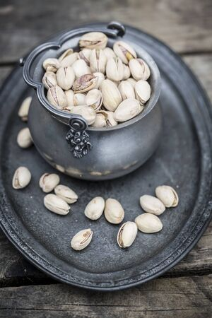 pistachios: Pistachios in zinc bowl on tray and wood Stock Photo
