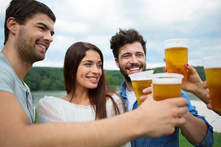 toasting: Group of friends toasting with beer in plastic glasses Stock Photo