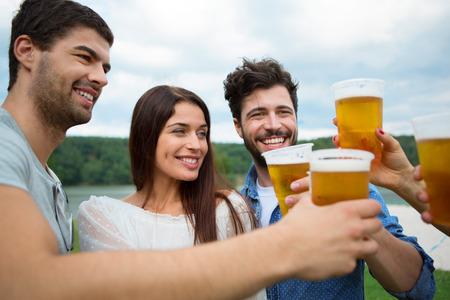 jovenes tomando alcohol: Grupo de amigos brindando con cerveza en vasos de pl�stico