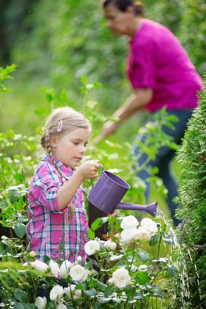twee: Girl helping granny in garden, waterin plants