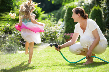 funny kid: Grandmother watering garden , girl jumping over water jet