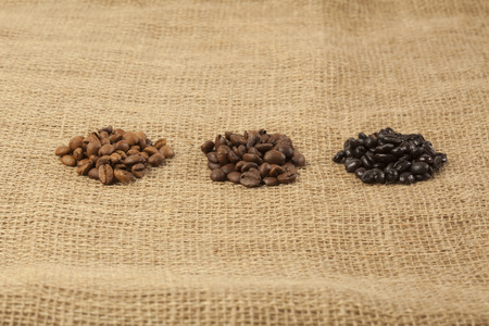 roasting: Different roasting grades of coffee beans in separate heaps on jute textile background Stock Photo