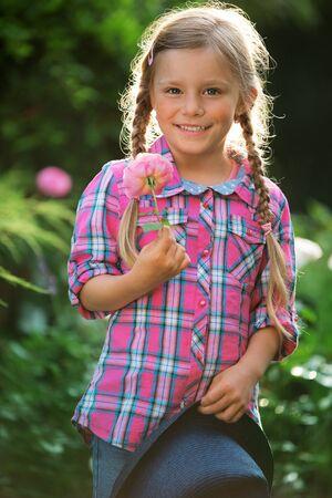 twee: Girl in garden holding flower Stock Photo