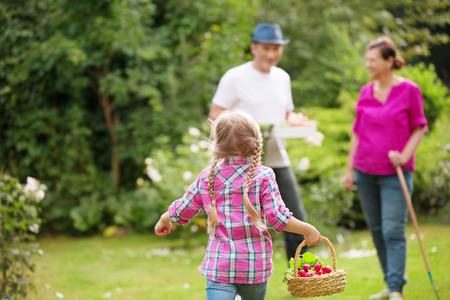 Family in garden, little girl running with basket in hand photo