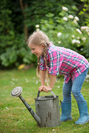 twee: Girl trying to lift heavy watering can in garden Stock Photo