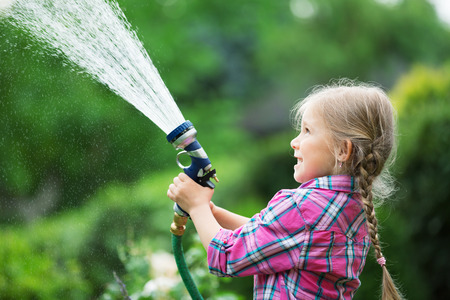twee: Girl watering flowers in garden with hose