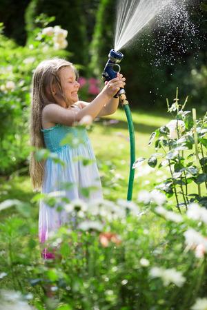 regar las plantas: Chica plantas con manguera de riego de jardines Foto de archivo