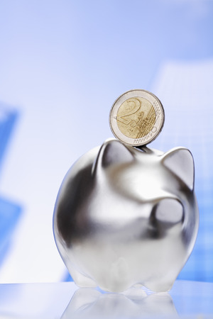 oldage: Piggy bank and euro coin against blue backgroud Stock Photo
