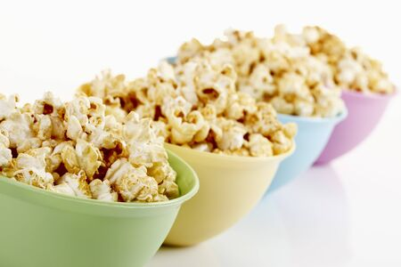 popcorn bowls: Popcorn in colorful bowls in a row on white background