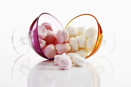 toppled: Colorful marshmallows in toppled glasses on white background Stock Photo