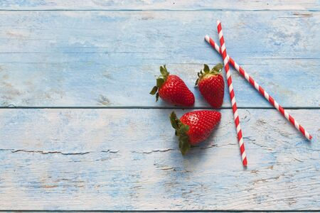 fresa: Fresas, pajitas para beber, madera azul