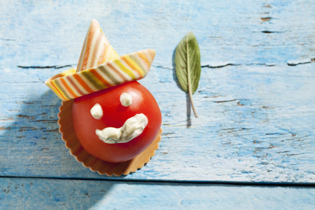 twee: Tomato, smiling face with Sombreroni noodle, sage leaf on blue wood