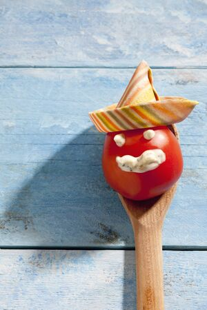twee: Tomato with smiling face with Sombreroni noodles on blue wood Stock Photo