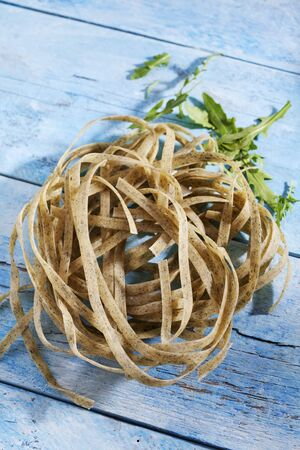 roquette: Raw Tagliatelle noodles with rocket on blue wood