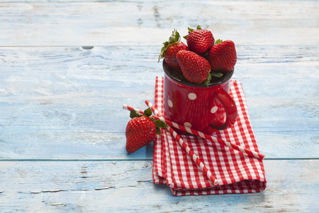 doiley: Strawberries in cup, napkin, drinking straws on blue wood