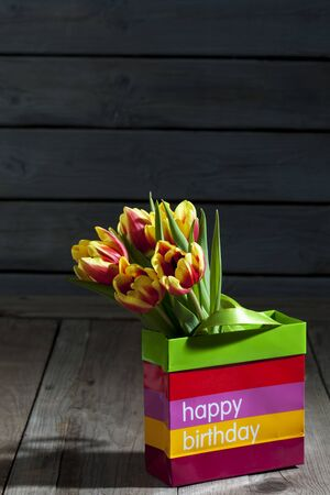 gift bag: Bouquet of tulips in gift bag, Happy Birthday Stock Photo