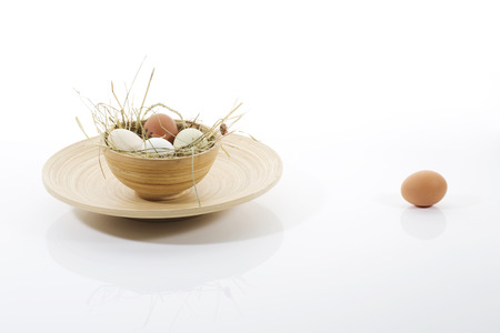 outsiders: Eggs in wooden bowl on plate, one egg isolated Stock Photo