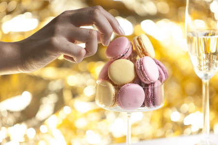 hand reaching: Hand reaching out for macarons in glass, glass of champain