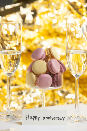 champain: Macarons in glass with champain glasses, Happy anniversary Stock Photo