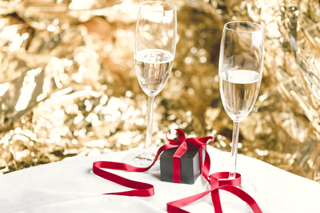 champain: Two glasses of champain and a present, golden background
