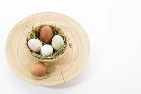 outsiders: Brown and white eggs in wooden bowl on plate Stock Photo