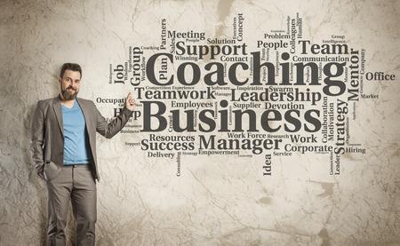 コーチング、ビジネス、単語雲グランジ壁に司会者としてビジネスの男性