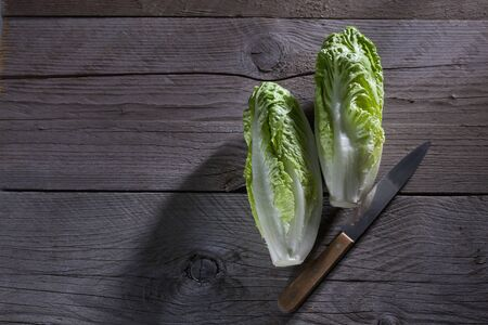 romaine: Romaine lettuces and knife on wood