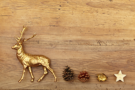Christmas decoration, deer figure, presents and cones on wood