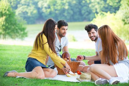 amigas: Grupo de amigos que tienen comida campestre en la pradera verde Foto de archivo