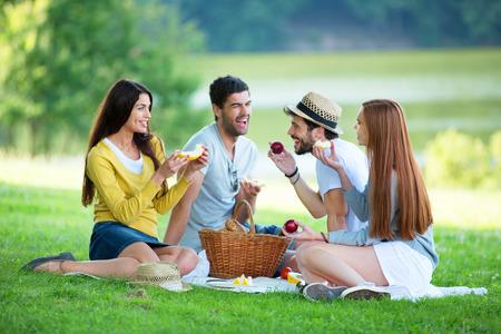 grupo de personas: Grupo de amigos que tienen comida campestre en la pradera verde Foto de archivo