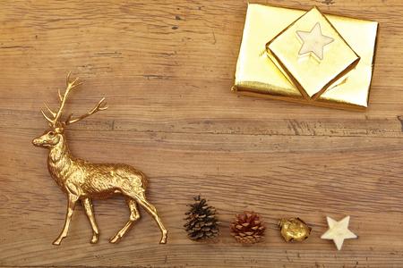 animal figurines: Christmas decoration, deer figure, presents and cones on wood