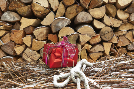 heap of snow: Christmas present in front of wood pile Stock Photo