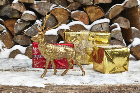 animal figurines: Christmas presents and deer figurine in front of woodpile