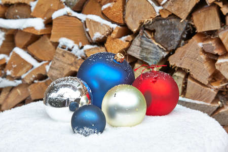 woodpile: Christmas baubles on table in front of woodpile